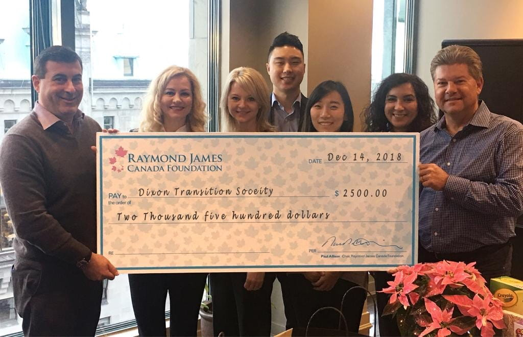 Group of people holding a large check